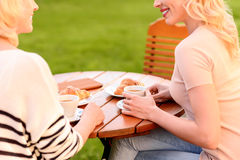 Friendly women enjoying communication in cafeteria. Cheerful mother and daughter are resting and talking in cafe outdoors. They are drinking coffee and smiling stock photography