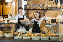 Friendly women and italian guy at bakery. Portrait of friendly women and italian guy at bakery display with pastry and fresh made loaves buns bread and cakes royalty free stock photography