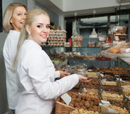 Friendly women selling nuts. And pastry in shop royalty free stock images