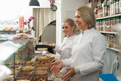 Friendly women selling nuts. Friendly women staff offering nuts and pastry in local confectionery royalty free stock images
