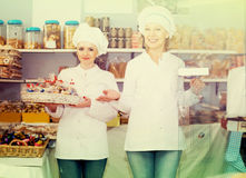 Friendly women staff offering sweets. In local confectionery stock images