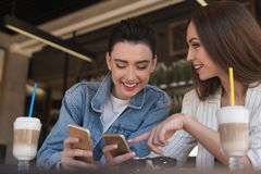 Friendly women using their smartphones. Girl sharing something on her phone with her friend royalty free stock photo