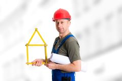 Friendly worker with yardstick- house and blueprint. Young worker with yardstick- house and blueprint Royalty Free Stock Photography