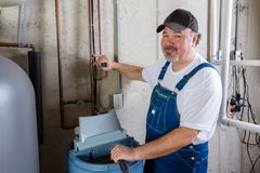 Friendly workman working on a water softener. Friendly smiling workman in dungarees installing or working on a water softener in a utility room turning to smile Royalty Free Stock Images