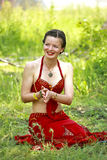 Friendly yoga instructor. Master classes, seminars on yoga, esoteric, tantra in nature. The young dark-haired woman smiling sitting on the grass in a red suit stock photos