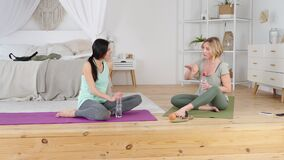 Friendly yoga trainer teaching young women to stretch her body