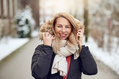 Friendly young blond woman outdoors in winter. Standing in a snowy road cuddling down into her warm woolly scarf and fur lined hood of her coat as she smiles at royalty free stock images