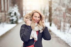 Friendly young blond woman outdoors in winter. Standing in a snowy road cuddling down into her warm woolly scarf and fur lined hood of her coat as she smiles at royalty free stock image