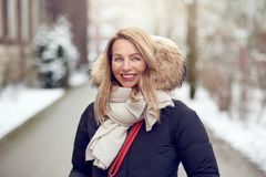 Friendly young blond woman outdoors in winter. Standing in a snowy road cuddling down into her warm woolly scarf and fur lined hood of her coat as she smiles at stock photo