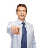 Friendly young buisnessman pointing finger Royalty Free Stock Photos