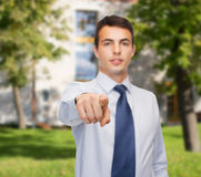Friendly young buisnessman pointing finger Royalty Free Stock Photo