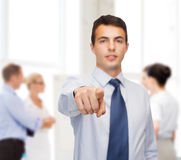 Friendly young buisnessman pointing finger Stock Photos