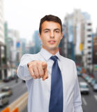 Friendly young buisnessman pointing finger Stock Images