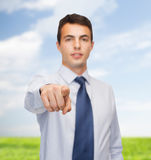 Friendly young buisnessman pointing finger Stock Photography