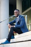 Friendly young businessman sitting on steps in the city Royalty Free Stock Image
