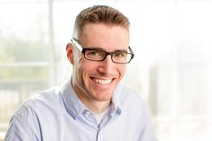 Friendly young businessman wearing glasses. Young friendly professional business man wearing glasses at the office Royalty Free Stock Images