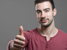 Friendly young casual man in red v-neck shirt showing thumb up gesture at camera Royalty Free Stock Images