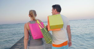 Friendly young couple walking on the pier after. Steadicam shot of young man and woman with shopping bags walking on the pier in the sea. Then they turning and stock video footage
