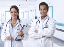 Friendly young doctors on hospital corridor smile Stock Image