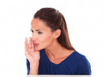Friendly young female in blue blouse whispering Stock Image