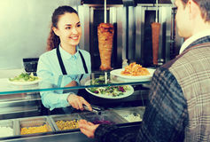 Friendly young female worker serving customer. With smile at shawarma place Royalty Free Stock Photos