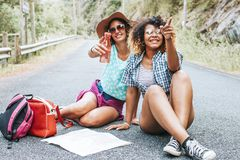 Girls trip with map on the road. Friendly young girls trip with map on the road, people on travel stock images
