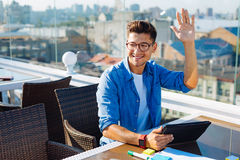 Friendly young guy waving hello to someone. Hello there. Happy minded gentleman wearing glasses raising his hand and greeting someone at a cafe while relaxing on Royalty Free Stock Photo