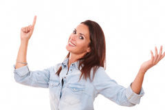 Friendly young lady pointing up and smiling Stock Photography