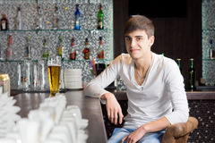 Friendly young man drinking in a bar stock images