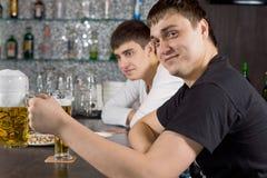 Friendly young man drinking beer at the bar Stock Photos