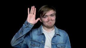 Friendly young man in jean jacket waving his hand to say goodbye, isolated on black background. Polite young man saying. Goodbye, waving his hand stock image