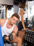Friendly young man making biceps curls in gym Stock Photo