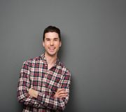 Friendly young man smiling with arms crossed Royalty Free Stock Image