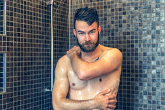 Friendly young man soaping himself in the shower Royalty Free Stock Photos