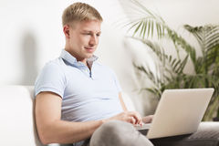Friendly young man working on laptop at home. Stock Image