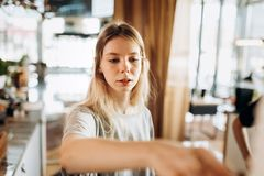 A friendly young slim girl with blonde long hair,wearing casual style,passes a coffee in a cozy coffee shop. stock images