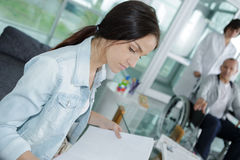 Friendly young woman behind reception desk administrator stock image