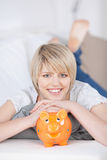 Friendly young woman with her piggy bank Stock Photos