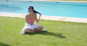 Friendly young woman relaxing near a pool stock footage