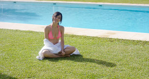 Friendly young woman relaxing near a pool Stock Photos