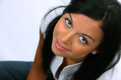 Friendly young woman sits and smiles. Friendly young woman sitting on the ground and smiles Royalty Free Stock Photography