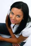Friendly young woman sits and smiles. Friendly young woman sitting on the ground and smiles Stock Photos