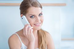 Friendly young woman talking on a mobile phone Royalty Free Stock Images
