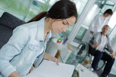 Friendly young woman behind reception desk administrator stock photos