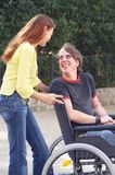 Friends. Girl is talking to a handicaped boy on a wheelchair Stock Photography