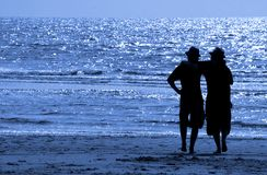 Friends. Two friends or brothers, arm in arm, on the beach Royalty Free Stock Photo
