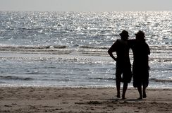 Friends. Two friends or brothers, arm in arm, on the beach Royalty Free Stock Images