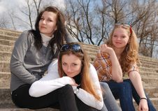 Friends. Three teenage girl sits on the stone stairs sunny day Stock Image