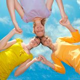 Friends. Three teenage girlfriends holding hands over blue sky background Stock Photo