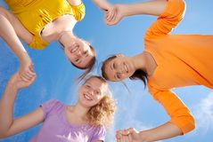 Friends. Three teenage girlfriends holding hands over blue sky background Royalty Free Stock Image